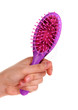 purple hair brush with lost hair on it isolated on white
