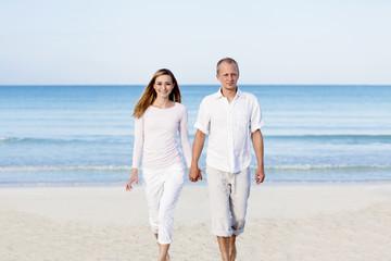 Junges Paar mit mann und frau im Sommer am Strand
