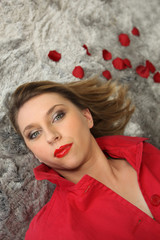 Woman laying on rug next to rose petals