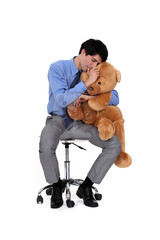 An adult businessman hugging a big teddy bear.