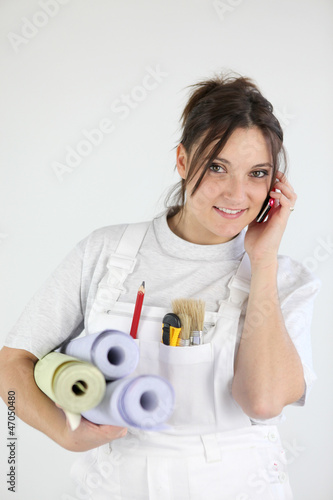Female decorator holding rolls of wallpaper