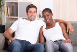 Mixed race couple sat on couch