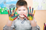 Boy with hands soiled in a paint