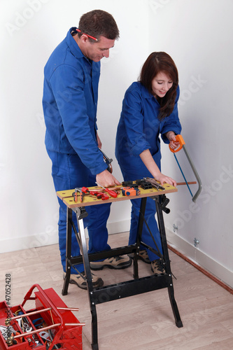 Worker showing an apprentice how to use a hacksaw