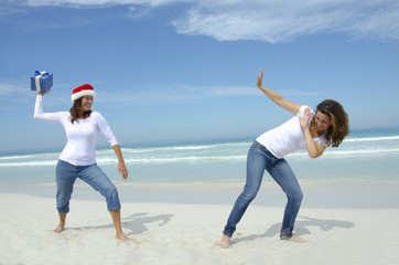Women / girls holiday fun with christmas present at tropical bea