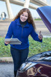 Woman showing thumb up standing in front of opened car cowling