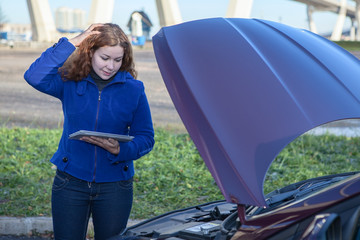 Thinking woman with opened car hood and tablet pc
