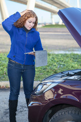 Thinking curly hair woman with opened car cowling and tablet pc