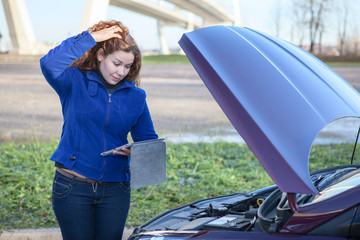 Broken vehicle with thinking woman with tablet computer near