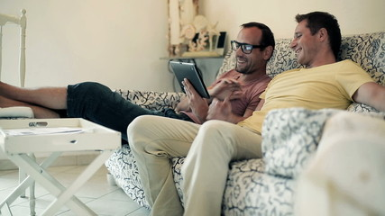Two male friends on sofa using electronic tablet