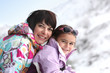 Mother and daughter on snowy mountain
