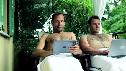 Two guys with laptop and tablet computer relaxing in spa resort,