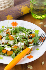 Salad with pumpkin, feta and arugula on a plate close up vertica