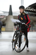 Female Cyclist With Courier Bag And Package On Street