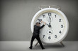 Businessman pulling a clock hand backwards - 47060619