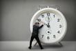 Leinwandbild Motiv Businessman pulling a clock hand backwards