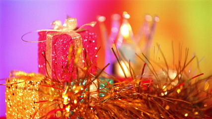 Christmas gift and candle on defocused lights background