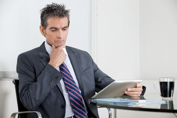 Contemplative Businessman Using Digital Tablet In Office