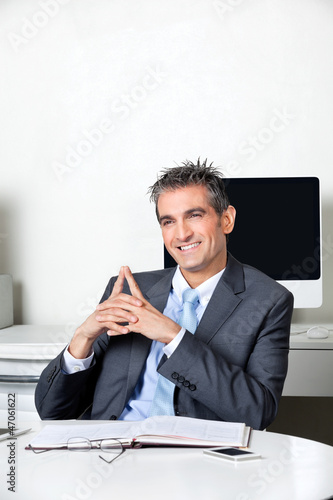 Thoughtful Happy Businessman At Desk