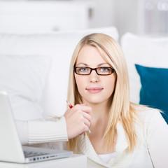 blonde frau sitzt mit laptop auf dem sofa