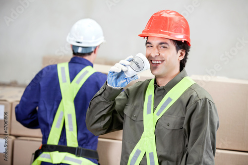 Foreman Drinking Coffee While Colleague Working At Warehouse