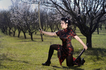 The geisha with katana in a garden