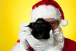 Aged Santa adjusting camera lens before click