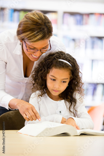 Schoolgirl reading with her teacher
