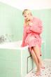 Gutaussehende junge Frau im Bademantel auf der Badewanne