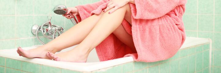Frau im Bademantel auf der Badewanne sitzend