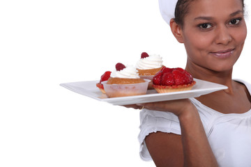 Bakery worker holding plate of fruit tarts