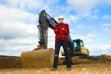 building worker in front of excavator