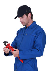 Tradesman adjusting a pipe wrench