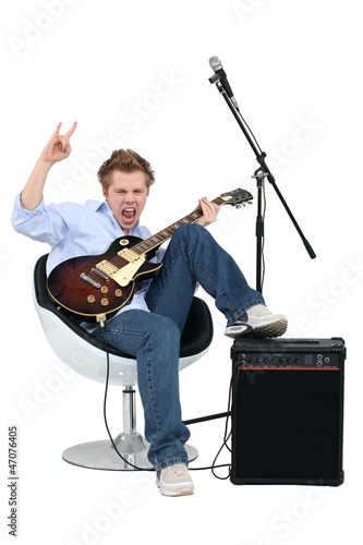 Young man with guitar playing rock music