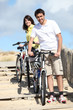Couple cycling by the beach