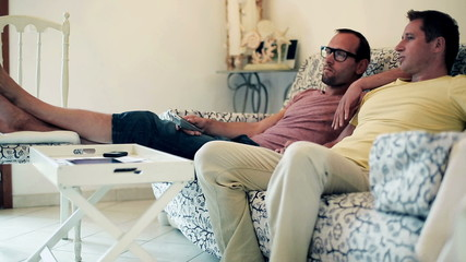 Two male friends on sofa watching television