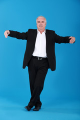 Businessman dancing alone on blue background