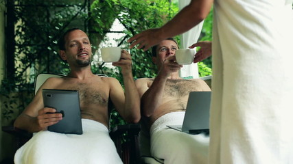 Happy friends with laptop and tablet computer relaxing in spa re