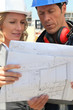 female architect and workman consulting blueprints