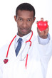 Hospital doctor with a plastic heart in the palm of his hand