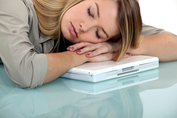 Blond woman asleep on laptop