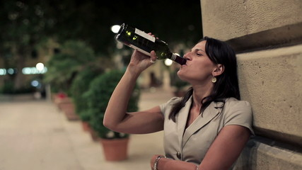 Young drunk woman drinking wine in the city, steadicam shot