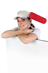Woman with a paint roller and blank board