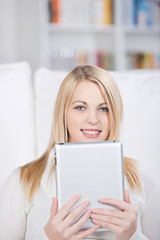 lächelnde junge frau liest am tablet-pc