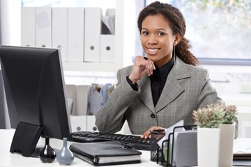 Portrait of happy businesswoman at desk