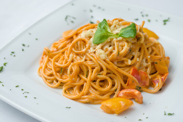 Spaghetti pasta with cream cheese sauce and tomatoes
