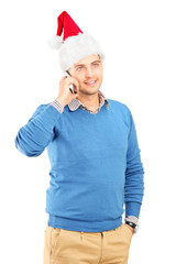 Casual guy wearing a santa hat and talking on a phone