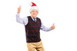 Happy mature gentleman with christmas hat giving thumbs up