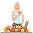 A smiling female holding a red apple behind a pile of different