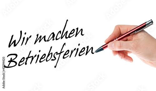 Hand mit Stift schreibt Wir machen Betriebsferien